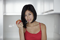 head shot of young woman holding red apple and smiling - Yukmin