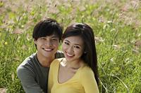 smiling couple outside in grassy field - Yukmin