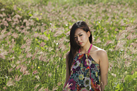 young woman standing in field of grass - Yukmin