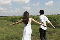 young couple walking in field holding hands, clouds with blue sky as background - Yukmin