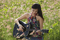 Woman playing guitar outside in grassy field. - Yukmin