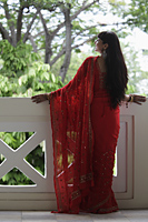 Back shot of Indian woman wearing a red sari looking over balcony. - Alex Mares-Manton