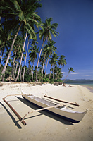 Philippines,Palawan,Bascuit Bay,El Nido,Couple Sunbathing on Beach with Outrigger Boat in Foreground - Travelasia