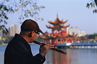 Taiwan,Kaohsiung,Man Playing Flute at Lotus Lake - Travelasia