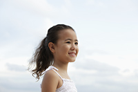 head shot of young girl smiling with clouds in background - Yukmin