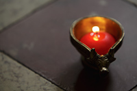 Lit candle in bronze cow dish - Alex Mares-Manton