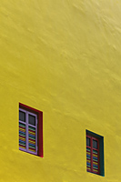 Yellow painted wall with bright colored windows - Alex Mares-Manton