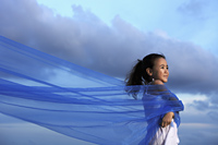 Young girl holding blue cloth blowing in the wind with blue sky background - Yukmin