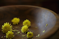 Close up of chrysanthemum flowers in wooden bowl. - Alex Mares-Manton