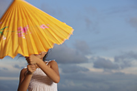 young girl trying to open up yellow umbrella - Yukmin