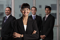 Indian woman smiling with arms folded in front of male colleagues - Alex Mares-Manton