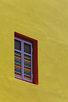 Close up of yellow painted building with bright colored shutters - Alex Mares-Manton