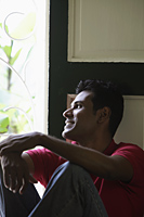 Indian man looking out window and smiling - Alex Mares-Manton