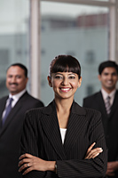 Indian woman smiling with arms folded in front of two colleagues - Alex Mares-Manton