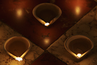 Lit clay oil lamps on floor - Alex Mares-Manton