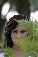Head shot of young woman looking through ferns - Alex Mares-Manton
