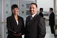 Indian man and woman in business attire smiling at camera. - Alex Mares-Manton