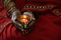 Close up of woman wearing red sari and holding lit candle - Alex Mares-Manton