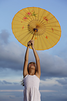 young girl holding up yellow Chinese umbrella, bluebsky background - Yukmin