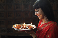 Profile shot of Indian woman holding a tray of lit oil lamps - Alex Mares-Manton