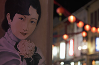 Poster of Chinese woman's face on wall with lanterns in background - Alex Mares-Manton