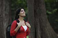 Young woman wearing a back pack looking up at trees and smiling - Alex Mares-Manton