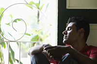 Indian man sitting near window with closed eyes - Alex Mares-Manton