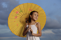 young girl smiling holding yellow Chinese umbrella, blue sky background - Yukmin