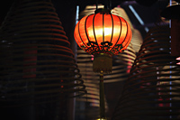 Red lantern with incense coils in foreground - Alex Mares-Manton