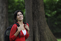 Mid shot of young woman wearing back pack and smiling - Alex Mares-Manton