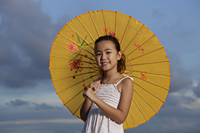 young girl holding yellow Chinese umbrella and smiling - Yukmin