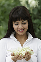 Head shot of woman looking at flowers in her hands - Alex Mares-Manton