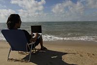 Rear view of man sitting on beach working on a laptop - Yukmin