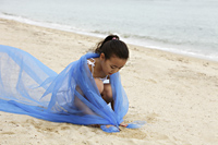 Young girl with blue cloth wrapped around her sitting on sand. - Yukmin