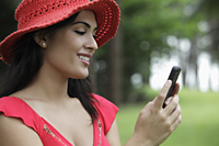Profile shot of young woman wearing a red hat and looking at her phone. - Alex Mares-Manton