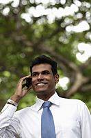 Portrait of Indian man talking on phone and smiling outdoors - Alex Mares-Manton