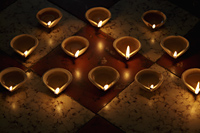 A group of lit clay oil lamps on floor - Alex Mares-Manton