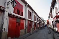 Narrow street with red doors in Macau - Alex Mares-Manton