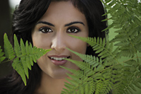 Head shot of young woman looking through ferns and smiling - Alex Mares-Manton