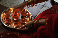 Close up of woman wearing a sari, putting oil lamps on silver tray - Alex Mares-Manton