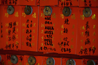 Different fortunes written on red paper at a Buddhist Temple - Alex Mares-Manton