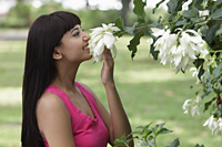 profile of young woman smelling flowers outside - Alex Mares-Manton