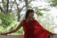 Indian woman wearing red sari leaning on balcony, smiling - Alex Mares-Manton