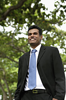 Indian man smiling outdoors with tree in background - Alex Mares-Manton