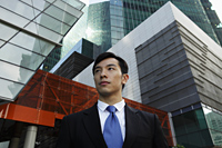 Young man wearing a suit standing in front of modern buildings - Yukmin