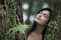 Head shot of young woman resting her head on a tree with eyes closed. - Alex Mares-Manton