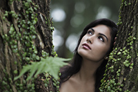 Head shot of young woman looking up with tree in foreground - Alex Mares-Manton