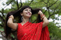 Indian woman wearing red sari smiling with hands in hair - Alex Mares-Manton