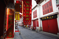 Red signs on narrow street in Macau - Alex Mares-Manton