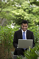 Indian man working on laptop with green plants and trees in foreground and background - Alex Mares-Manton